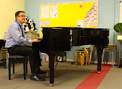 ISH Head of School, Mr. Cross tries out the new grand piano